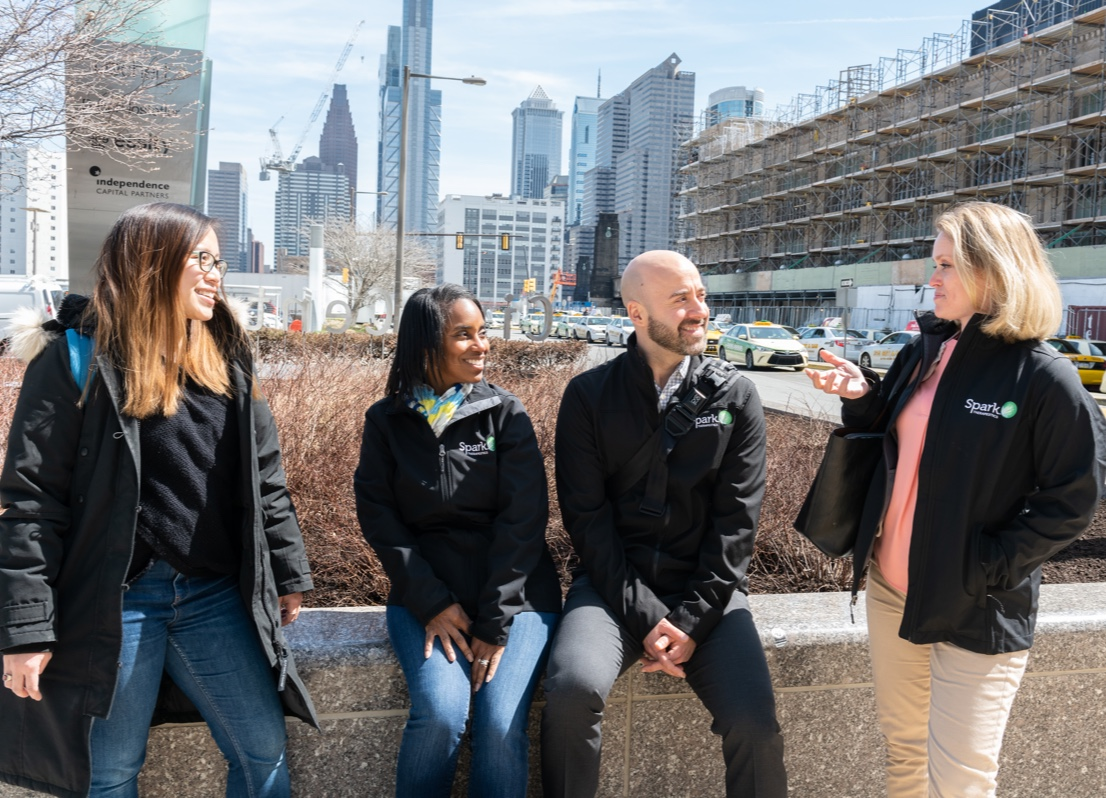 Group of four Spark Therapeutics Medical Affairs team members outdoors with center two seated on a low wall and outer two standing, looking at one team member and smiling with city skyline in background